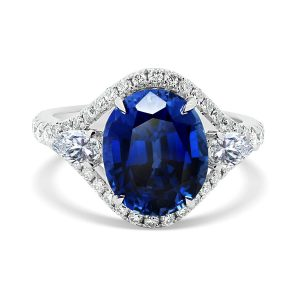 Acacia Blue Oval sapphire ring with pear cut side stones and delicate prong set outer halo