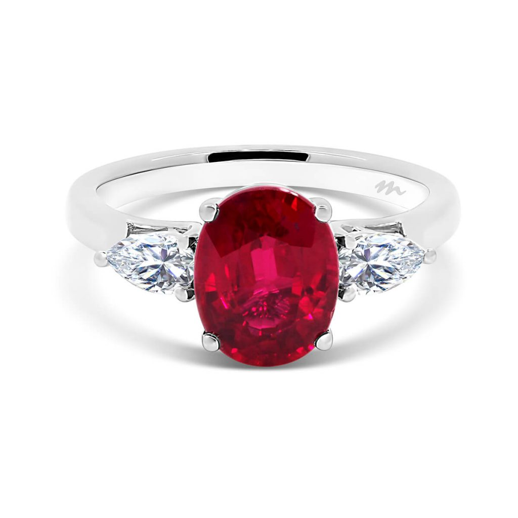 Cassic Red oval ruby trilogy with pear cut side stone on tapered band