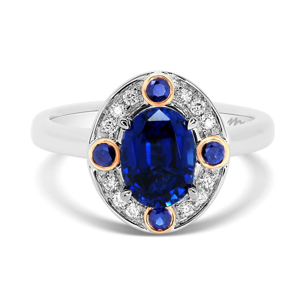 Clover Oval Blue halo design in two-tone gold with lab-grown sapphire centre stone & halo with 4 bezel set sapphires