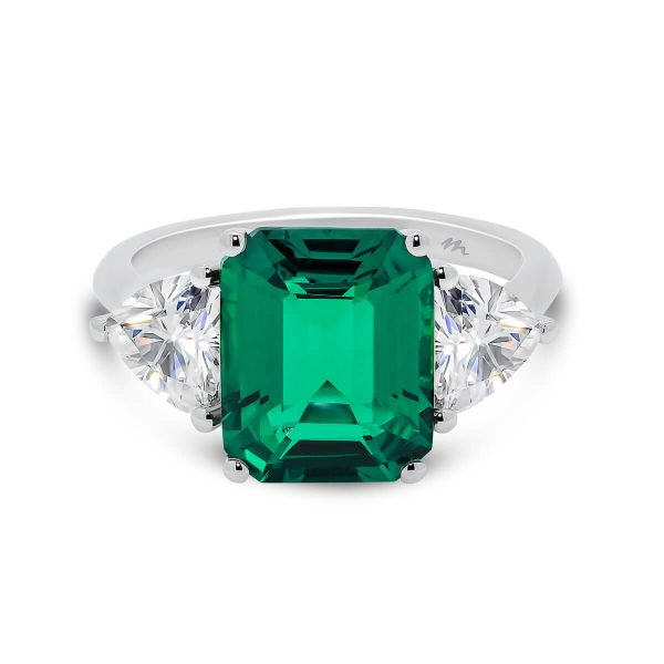 Tulip emerald trilogy with two trillion side stones on knife-edge band