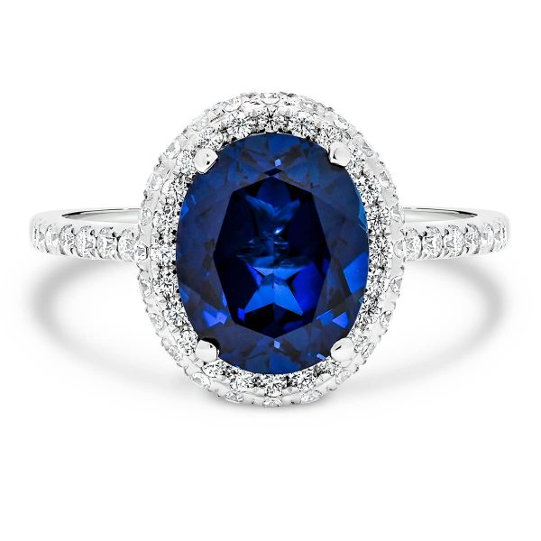 Violet oval sapphire halo ring with rolling-edge halo and stone-set bridge on prong set half band
