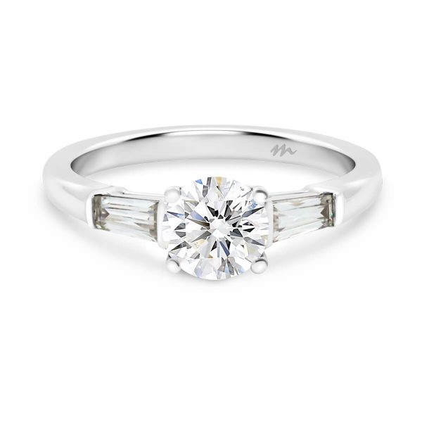 Georgina round trilogy ring with tapered baguette side stones on a plain polished band